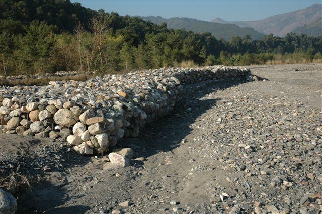 Bouwen van dammen in een rivier die in de regentijd tientallen dorpen afsluit van de bewoonde wereld. En dat niet alleen, maar ook het landbouwgrond van de arme boeren meeneemt naar...?